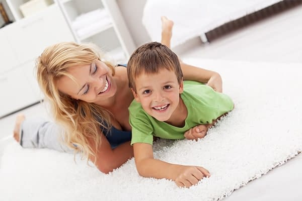 mom and son on freshly cleaned rug