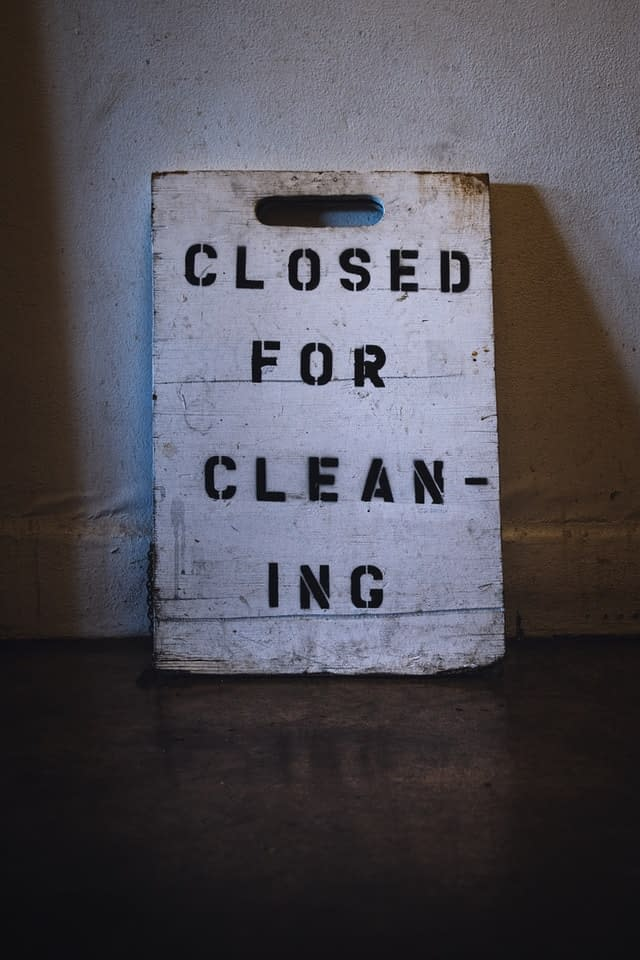 Closed for cleaning sign on a white wooden board