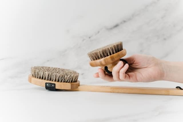 A person holding a brown wooden brush for scrubbing before applying deep cleaning advice to their home.