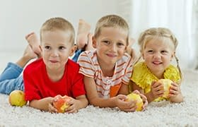 3 kids on carpet with apples