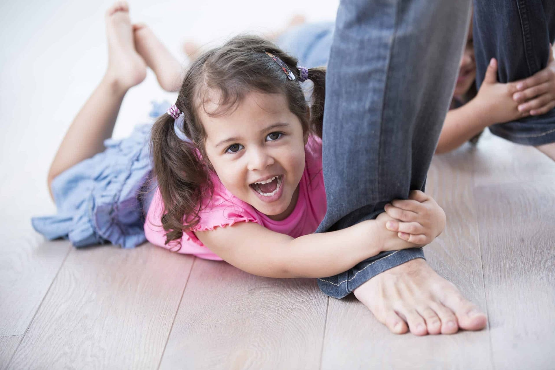 girl clinging to dad on wood floor