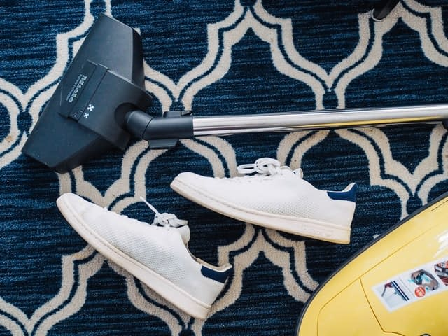 A vacuum cleaner and shoes on a carpeted floor.