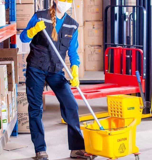 A woman standing in a cleaning uniform with a bucket.