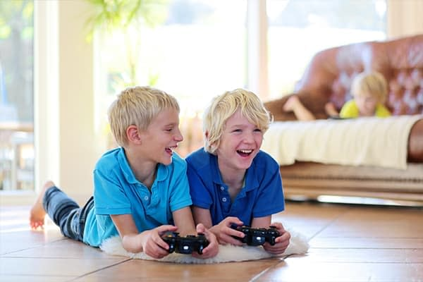 two boys playing video games on clean tile